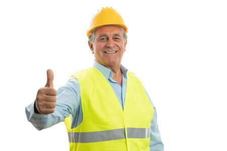 Smiling old builder making thumb up gesture as like wearing safety vest and helmet isolated on white