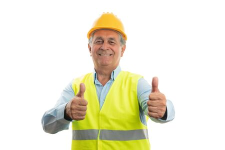Happy builder man showing double like gesture with thumbs wearing vest and helmet isolated on white studio background