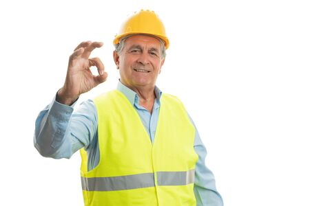 Old builder man with friendly expression making okay gesture using fingers isolated on white studio background