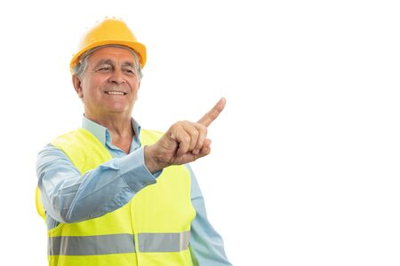 Smiling elder male builder touching invisible copyspace on display using index finger isolated on white
