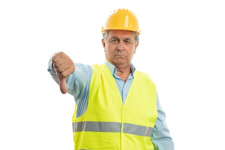 Angry male builder showing thumb down as dislike gesture isolated on white studio background