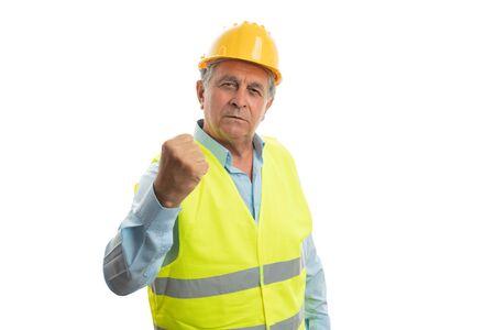 Trabajador de la construcción masculino agresivo sosteniendo el puño como concepto de lucha aislado sobre fondo blanco de estudio Foto de archivo