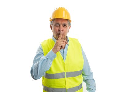 Old male builder with serious expression touching index finger to mouth as shush gesture isolated on white background