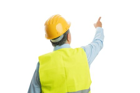 Old male builder pointing index finger at blank copyspace with back to camera isolated on white studio background