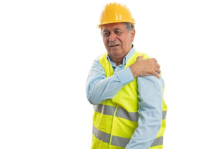 Old male builder touching painful arm as physical effort concept isolated on white background Stock Photo