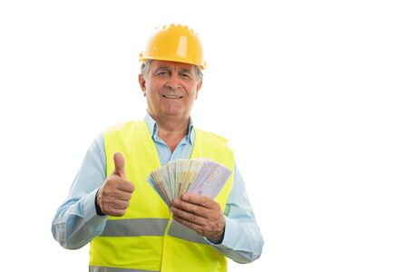 Happy old male engineer holding money and showing thumb up as like gesture isolated on white studio background