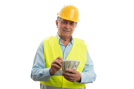 Cheerful old male architect wearing fluorescent vest and hardhat counting dollars isolated on white studio background