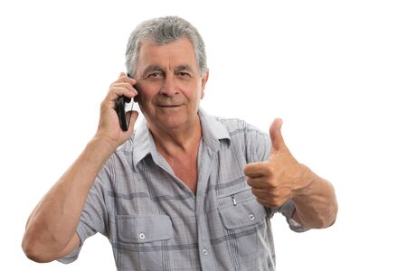 Smiling old man with gray hair making okay gesture while speaking on the phone isolated on white background