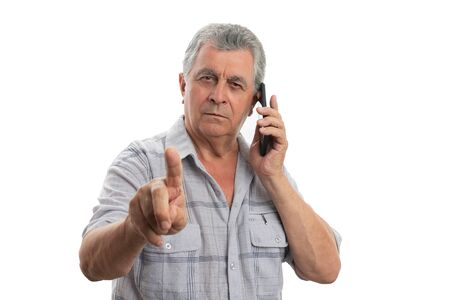 Busy old man with  gray hair making hold on gesture while talking on the phone isolated on white background