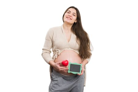 Smiling pregnant woman holding heart toy and green blackboard isolated on white