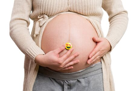 Close-up of pregnant woman holding heart-eyes emoji in front of her belly isolated on white background as love concept