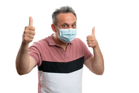 Male wearing medical disposable mask showing thumbs-up gesture as hope to protect against covid or corrona virus concept