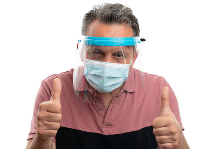 Adult man wearing transparent screen and protective mask showing thumbs up as like gesture in sars covid19 influenza pandemic isolated on white background