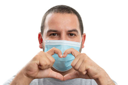 White adult man making heart symbol with hands as love safety healthcare concept wearing medical or surgical face covering preventing covid19 sars influenza concept isolated on studio background Stockfoto
