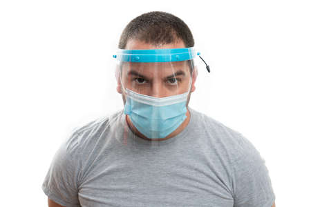 Close-up of adult male model wearing transparent face shield screen and medical or surgical disposable mask as covid19 influenza sars pandemic prevention concept isolated on white background