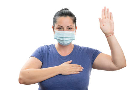 Adult woman making honest oath gesture with palm up and hand on heart wearing disposable medical or surgical covid19 virus mask covering isolated on white background