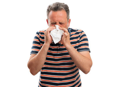 Close-up of adult male model wearing fashionable summer outfit sneezing covering mouth and nose with white tissue as covid19 ill cold flu concept isolated on studio background Banque d'images