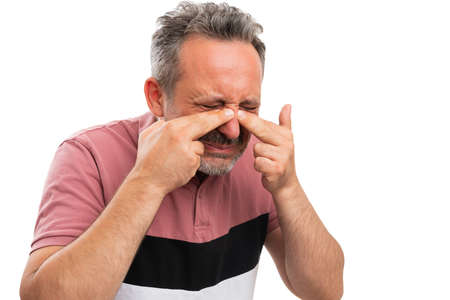 Sick adult man model wearing casual summer stylish tshirt touching nose as sinuses pain gesture cold flu ill concept isolated with blank copyspace isolated on white Stock Photo