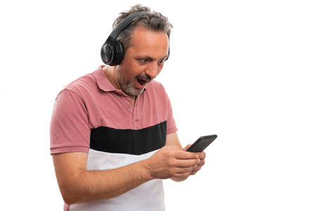 Male model looking at smartphone screen as listening to music in headphones making surprised wow amazing expression wearing casual summer attire with copyspace isolated on white