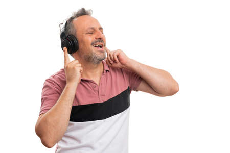 Cheerful adult male model smiling as listening to music in headphones singing dancing wearing colourful summer attire with blank copyspace isolated on white background