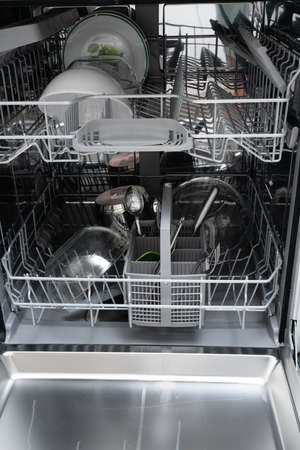 Close-up of open dishwasher machine with clean cutlery and plates as domestic appliance convenient timesaving for housechores