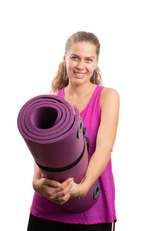 Fit woman with friendly smiling happy expression wearing pink sports training workout tanktop holding yoga or pilates mat as active healthy lifestyle concept isolated on white background