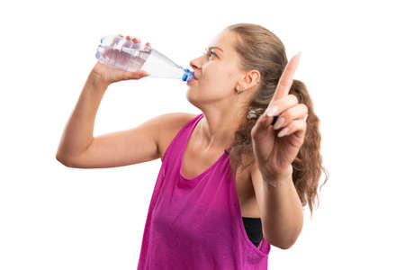 Sportive fit adult female drinking water from bottle making wait busy gesture using index finger wearing pink tanktop as gym training attire isolated on white studio background Imagens