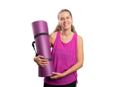 Adult woman smiling as training in sports attire pink tanktop holding yoga mat as pilates fitness concept with blank copyspace isolated on white studio background