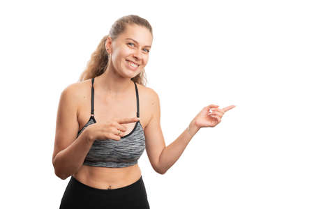 Fit adult woman wearing sport workout clothing smiling as pointing index fingers at blank copyspace for advertising active lifestyle concept isolated on white