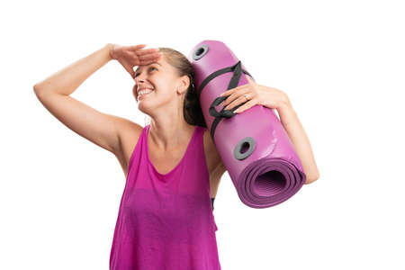 Cheerful sportive adult woman wearing athletic gym tanktop sportswear making searching gesture holding yoga or pilates mat isolated on white studio background