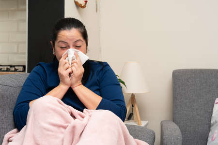 Sick adult woman with cold flu symptoms laying on couch blowing nose using napkin as pandemic stay home concept
