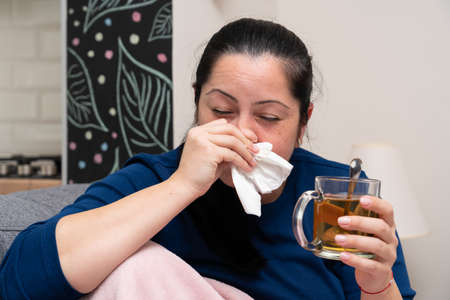 Adult woman model blowing runny nose while drinking medical tea from glass mug for covid19 influenza cold or flu symptoms