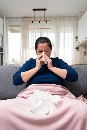 Sick woman with sars covid flu symptoms sitting on sofa holding stack of napkins on blanked at home as sinusitis concept