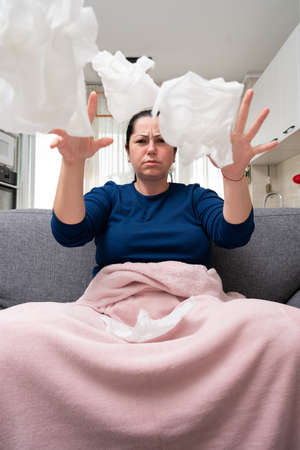 Sick adult woman model sitting on sofa at home throwing away napkins after sinusitis cold flu infection symptoms