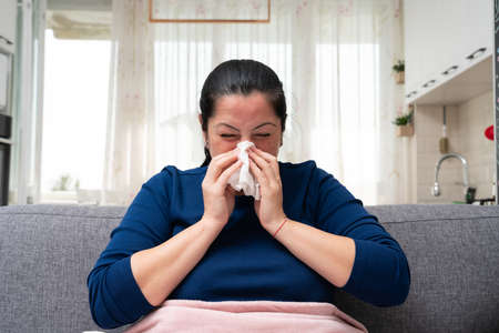Ill adult woman on home sofa blowing stuffy nose feeling unwell with cold influenza virus infection symptoms Imagens