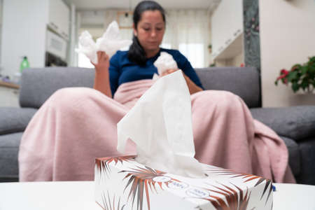 Close-up of napkins or handkerchiefs pack on table with sick adult woman sitting on couch in background having cold flu infection symptoms