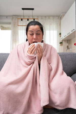 Woman having sinus infection sneezing holding napkin in hand as cold or flu virus infection symptom sitting on sofa Imagens