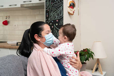 Cute baby daughter hugging mother female model with sars covid virus infection symptoms covering face using medical or surgical mask to protect child as pandemic concept