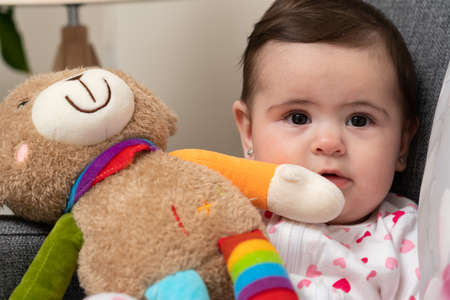 Close-up of happy baby girl smiling as playing with cute colourful teddy bear toy as childhood family time concept