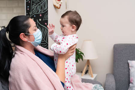 Adult female model as mother playing with cute baby girl wearing face medical or surgical mask covering nose and mouth to prevent cold flu covid19 sars virus infection Imagens