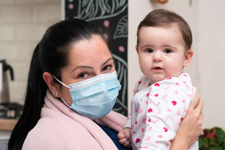 Female model as sick mother wearing medical or surgical mask to prevent covid19 flu influenza virus infection holding baby girl as pandemic family time concept Imagens