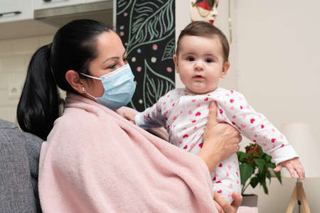 Ill mother having sars influenza flu symptoms covering mouth and nose with surgical or medical disposable mask holding cute baby girl as pandemic concept