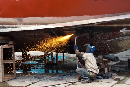Worker cutting ship iron plate