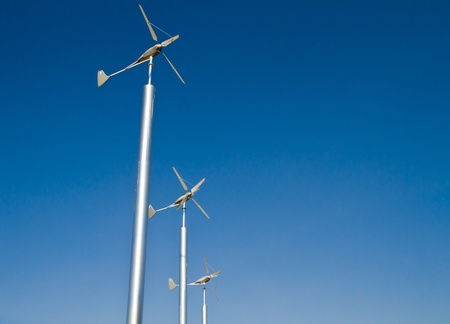 Three wind turbine against blue sky photo