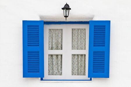 Blue window and lamp on white house photo