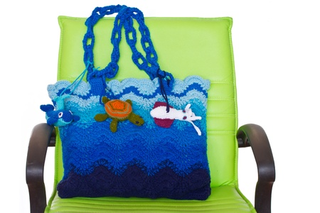Crochet handbag and green chair isolated on white background photo