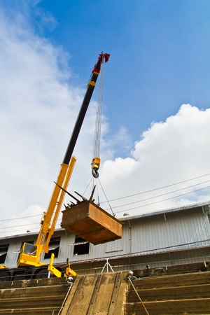 crane parts: Mobile crane is lifting tray over dockyard