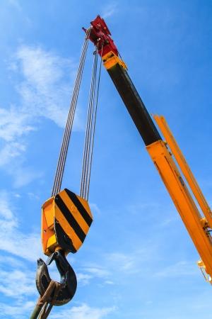 Hydraulic crane beams against blue sky Stock Photo