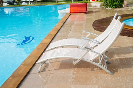 White lounges next to a swimming pool photo