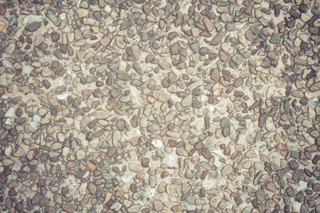 Old cement floor surface covered with stones photo